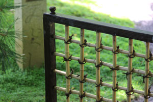 Image of homemade bamboo fencing, with timber frame and cupboard knob as decorative finial