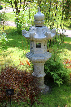 Photo showing a large granite Kasuga lantern, next to bamboo