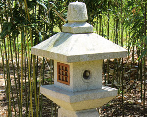 Image of an Oribe style granite lantern, with the column partially buried in the ground
