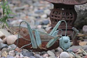 Picture of rusty grasshopper standing on pebbles, in front of metal shrine lantern