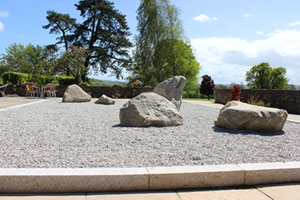 Picture of outdoor Japanese rock garden, with large trees in the background